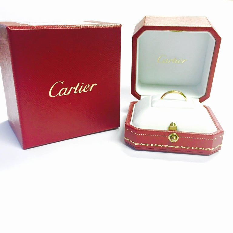 Elegant wedding band ring by Cartier. Crafted in 18K yellow gold in a high polished finish and has one 0.02 ct round brilliant cut diamond flush set at the front.   Hallmark: Cartier Au750 YR4553 Measurements: 2.5mm Width Size: US: 7.25 European: