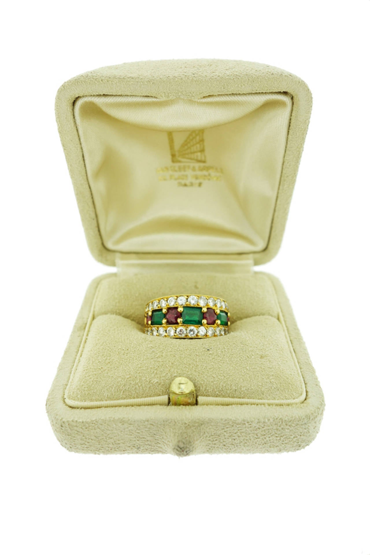 Classic Van Cleef & Arpels Vintage 18K Yellow Gold Emerald, Ruby and Diamond Ring. Circa 1970's.  The tapering design features natural Emeralds and Rubies alternating in the center, framed by two rows of diamonds. 