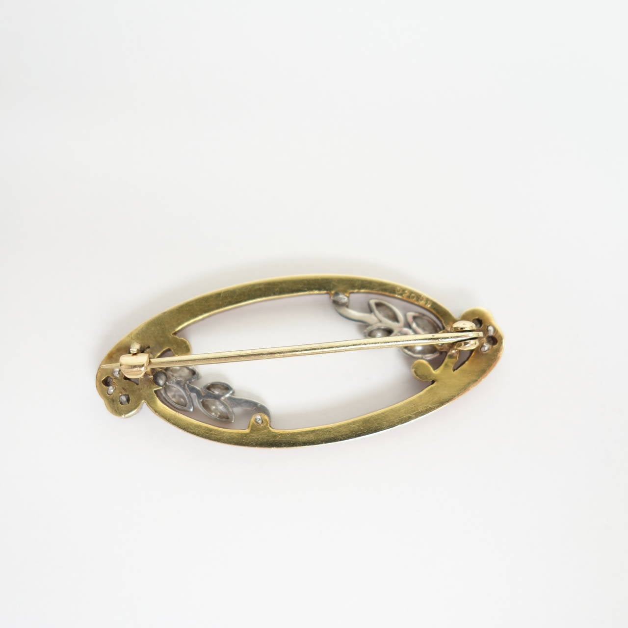 An elongated swirly design, composed of an 18K yellow gold red enamel frame decorated with diamond set platinum leafs on wine . Approximate total diamond weight: 0.50cttw. Color: G-H, Clarity: VS1-VS2. The brooch is in excellent condition, no damage