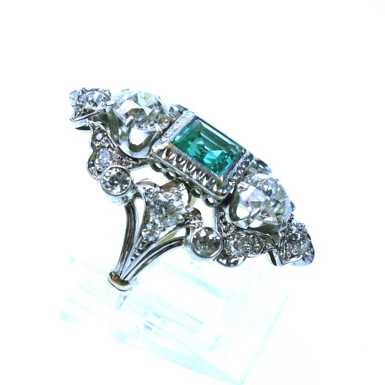 Fairy ring from the Edwardian era. An elongated design, featuring an approximately 1.00ct square cut bezel set natural emerald and two large old european cut diamonds in the center, accented by bezel and bead set diamonds in an open work setting.