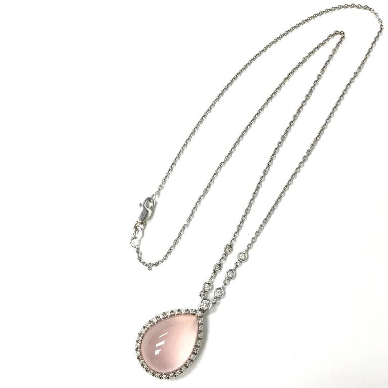 Favero stationary pendant necklace. Crafted from 18K white gold, featuring a teardrop shape rose quartz cabochon approx. 10.0ct, set within a bezel of diamonds, supported by a 16 inch length roll style chain set with seven bezel set round brilliant