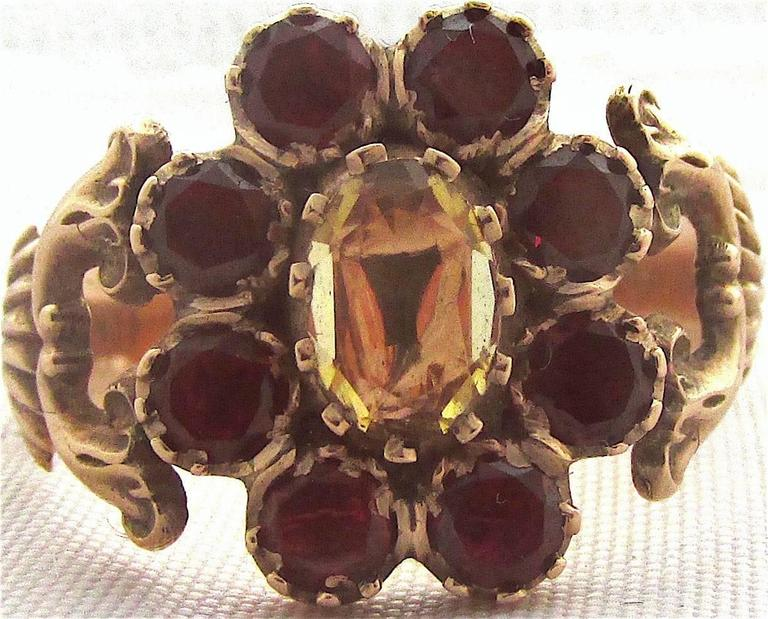 Delightful Georgian cluster ring in flower form set with eight almandine garnets and a center topaz in a scrolled 9K gold setting. The ring is a size 9.5 and dates to 1820. It measures approximately 5/8 at its widest.