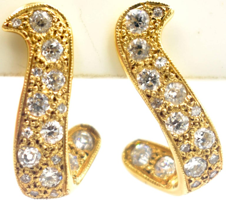 Delightful pair of 14K gold and diamond earrings in a softly swerving shape with screw back fittings. The clear, sparkly diamonds amount to 1.25 cts. But the weight is not what it's all about.  It's the intricacy of the design and the detail of the