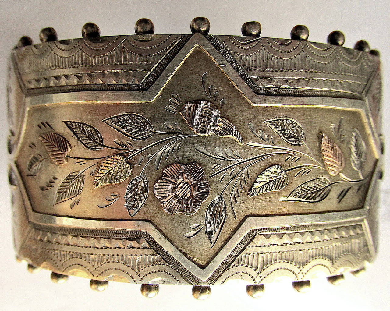 """Victorian silver and two-color gold cuff bracelet with an intricate floral design highlighted in a frame and bordered by an engraved scalloped design and beads. The interior measurement of the bracelet is 2"""" by 1 3/4"""" and it is 1 3/8"""" wide. A bold"""
