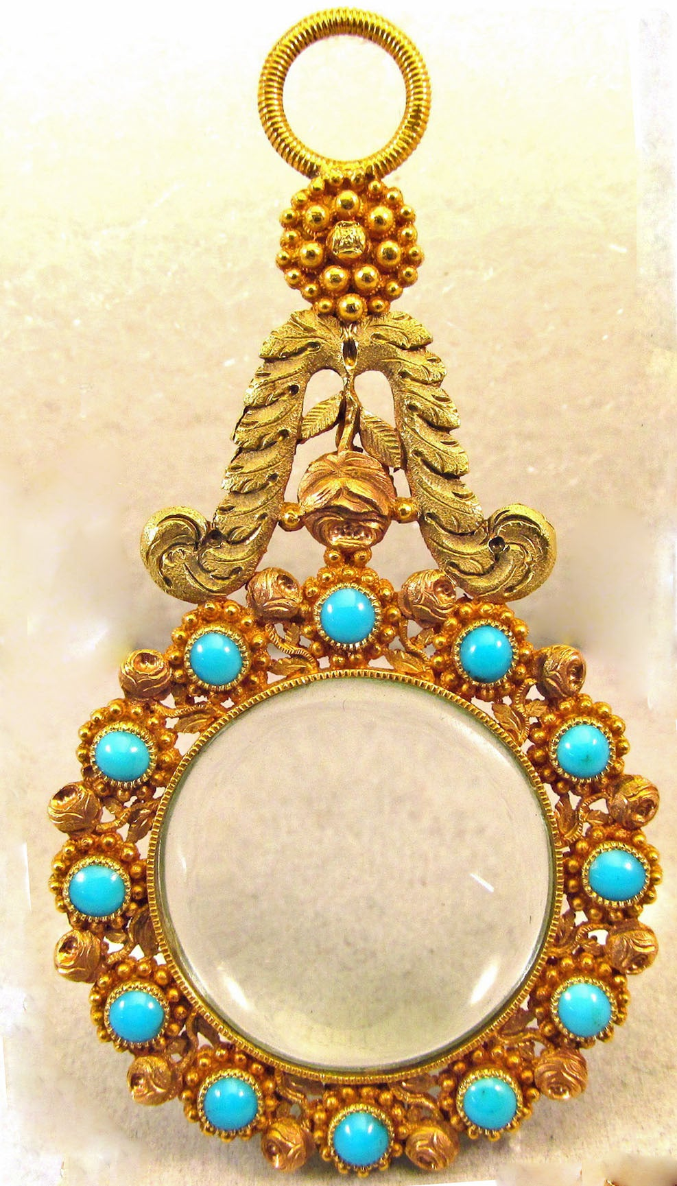 Unique Georgian quizzing glass or quizzer in three color 18K gold set with turquoise in a floral and leaf motif. The elaborate cannetille gold work is known for its intricate beads and coils and filigree. It became fashionable in England beginning