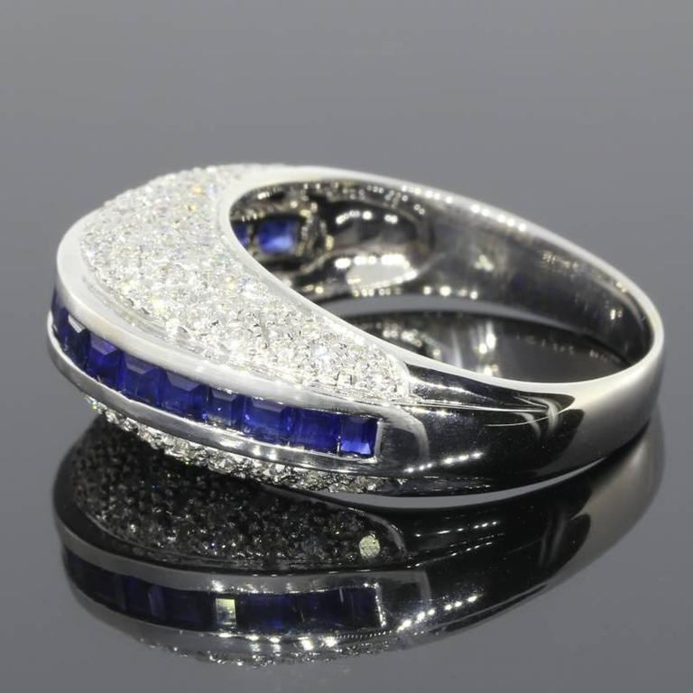 This beautiful & unique band ring features natural, AAA quality, princess cut, blue sapphires & sparkly, GH/SI quality, round brilliant cut diamonds. The sapphires are channel set in the center of the ring. The diamonds are pave set on the top &