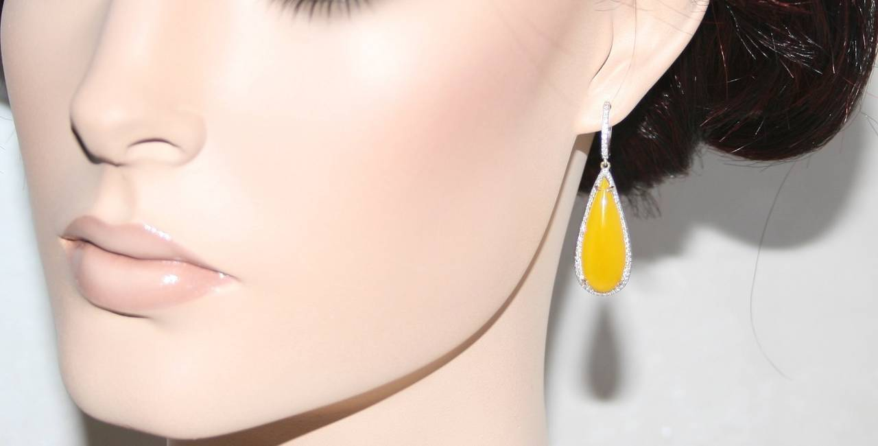 """A pair of brand new beautiful drop earrings. The earrings are yellow agate surrounded by diamonds. Set in 18K yellow gold weighing 7.9 grams. 0.35ct of Diamonds 21.00ct of Yellow Agate The earring measure 1.75"""" x 0.5""""."""