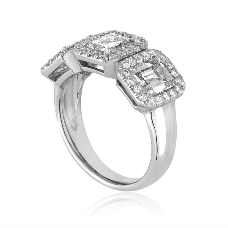 3 Stone Emerald Cut Diamonds Set in 18K White Gold Ring The 3 Emerald Cut Diamonds 2.30Ct I VS The 3 stones are surrounded small Diamonds. There are 0.50Ct Small Diamonds G VS. The ring is a size 6, sizable. The ring weighs 7.2 grams