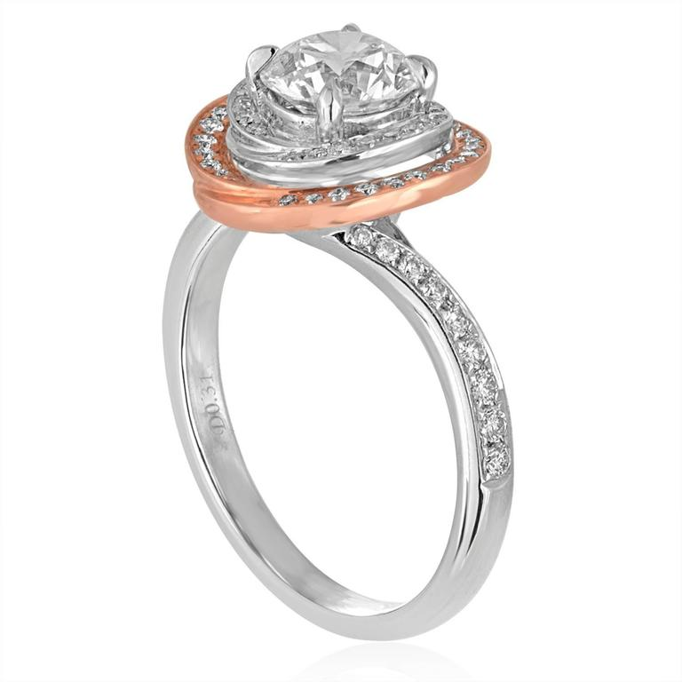 The ring is 18K White & Rose Gold Halo Engagement Ring The center stone is GIA Certified 1.05 Ct F VS2 The Halo & Band has 0.31 Ct in Diamonds E/F VS Size 6.5, sizable The ring weighs 4.5 grams