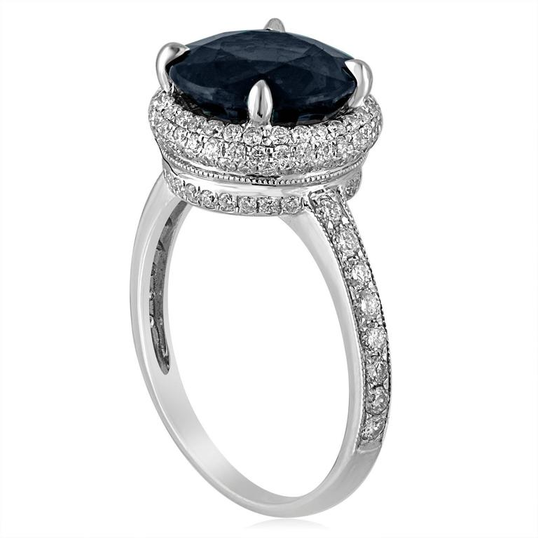 One-Of-A-Kind Sapphire Ring. The ring is 18K White Gold. The center stone is 4.98 Carat Round Greenish Blue Sapphire. The sapphire has NO HEAT and is certified by LAPIS. There are 0.91 Carats in Diamonds F/G SI. The ring is a size 6.75,