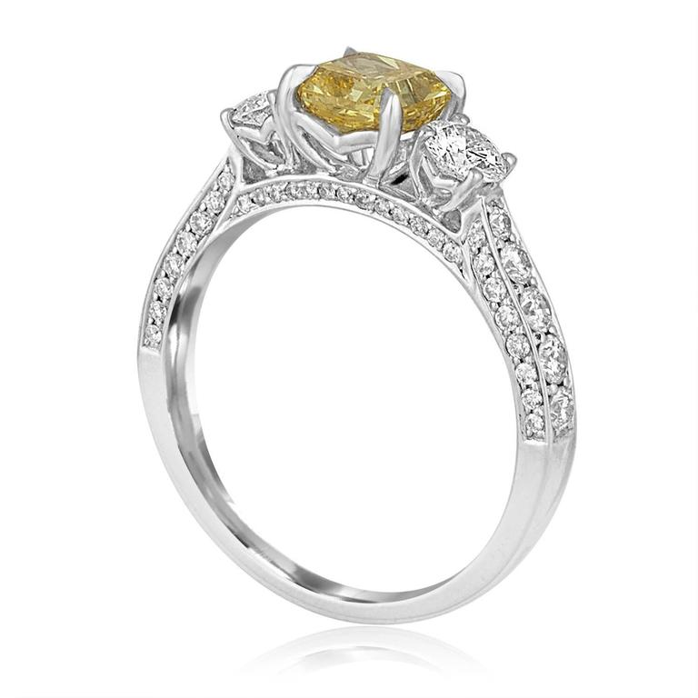 Stunning 3 Stone Engagement Ring The ring is 14K White Gold The center stone is GIA Certified Diamond The stone is Radiant Cut Fancy Intense Yellow 0.91 Carat VS2 The side stones are 0.34 Carats F SI There are small stones on the band 0.43 Carats F