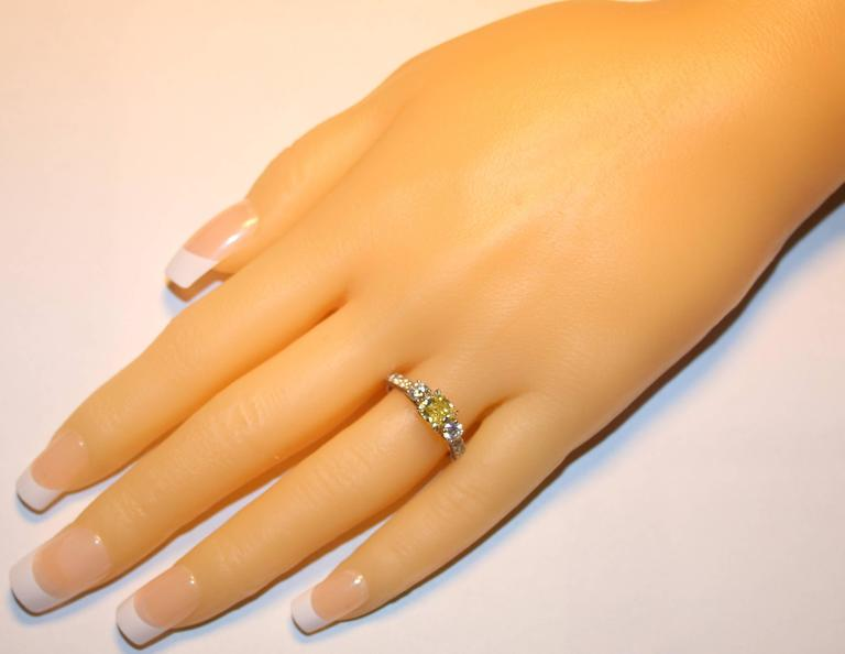 Contemporary GIA Certified 0.91 Carat Fancy Intense Yellow Diamond Three Stone Gold Ring For Sale
