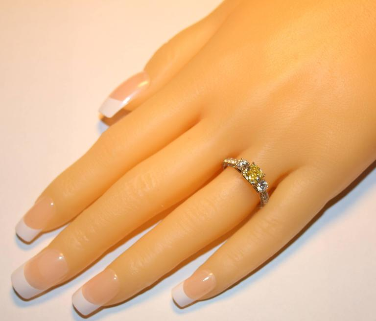 Radiant Cut GIA Certified 0.91 Carat Fancy Intense Yellow Diamond Three Stone Gold Ring For Sale