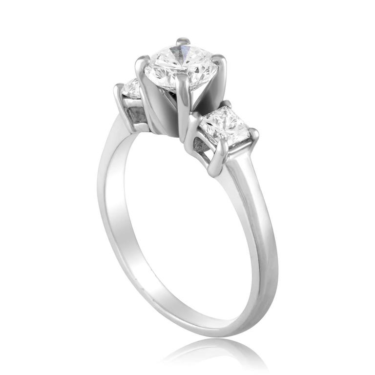 The ring is Platinum 950 The center stone is a Round Brilliant Diamond The Center stone is GIA Certified 0.90 Carats H VS2 The 2 Side stones Princess Cut Diamonds 0.50 Carats Total Weight G VS All 3 diamonds total 1.40 Carats. The ring weighs 5.8