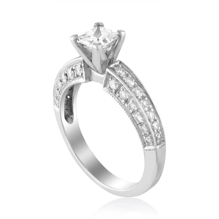 Solitaire Engagement Ring With Milgrain Pave. The ring is Platinum & 18K White Gold. The center Is Princess Cut Stone, GIA Certified 0.71Ct E VVS2. There are 0.15 Carats in small round diamonds F VS. The ring is a size 6.5, sizable. The ring weighs