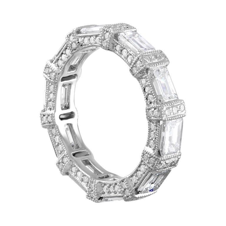 Very Unusual Emerald Cut Diamond Band. The emeralds are laid out in east to west for a very different look. The band is Platinum. There are 4.00 Carats in Emerald Cut Diamonds F/G VS. There are 1.18 Carats in Small Round Diamonds F/G VS. The ring is