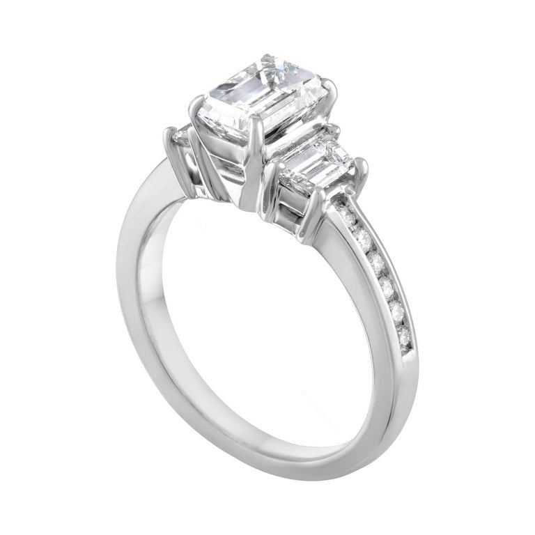 3-Stone Diamond Ring. The ring is 14K White Gold. The center stone in an Emerald Cut Diamond. The center stone is GIA Certified Diamond 1.16 Carats G VVS2. The 2 side stones are Trapezoids Diamonds 0.50 Carats G VS. There are 0.20 Carats in Small