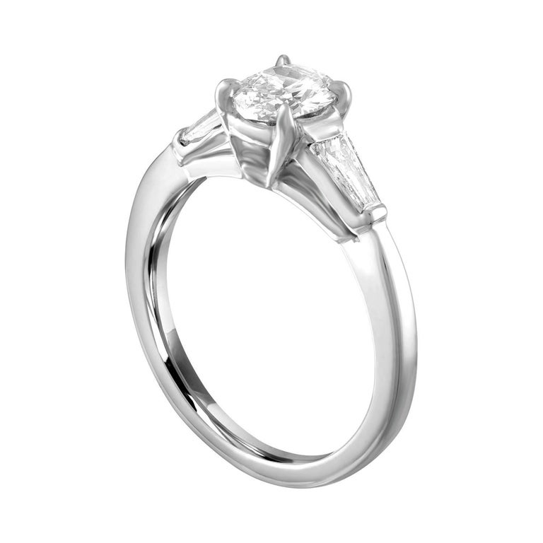 Oval Shape Engagement Ring. The ring is Platinum. The center Stone is an Oval 0.51 Carats F VS. There are 2 Tapered Baguettes 0.50 Carats F VS. The ring is a size 5.00, sizable. The ring weighs 3.9 grams.