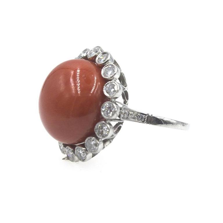 This fabulous estate ring features a beautiful color coral gemstone surrounded by diamonds. There are 18 diamonds that equal =.80 ctw, and another .08 ctw of diamonds in the shank. The head of the ring measures 22mm in diameter, and the ring is