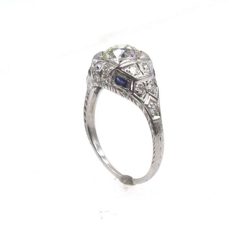 Beautiful Art Deco diamond ring crafted in platinum. The ring is set withan 1.31 carat Old European Cut diamond graded J color and SI2 clarity. The mountingfeatures diamonds ( approximately .25 ctw) and sapphire accents and measures 10mm in width
