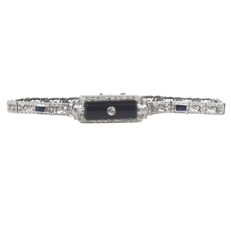 This beautiful platinum filigreebracelet features a rectangular onyx gemstone, diamonds, and accent sapphires. The 33diamonds equal approximately .50 carat total weight.The bracelet measures 7 inches in length and 10mm in width.