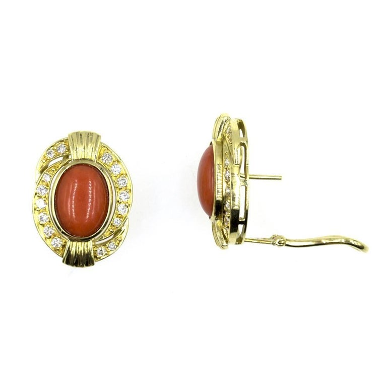 Colorful and rich red coral and diamond earrings.  These stunning earrings feature red cabochon coral surrounded by diamonds and 18 karat yellow gold. The surrounding 32 round brilliant cut diamonds, totaling .65 carat total weight, are graded G