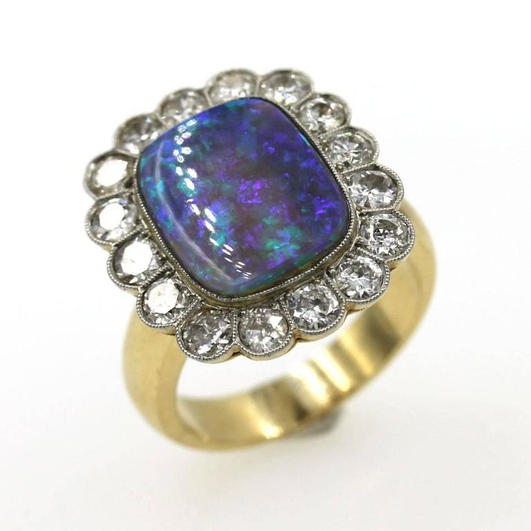 This fabulous black opal and diamond ring features 16 Old European cut diamonds that equal 2.25 carat total weight. The diamonds surround an approximately 5 carat high quality black opal. The ring is 18 karat yellow gold, and currently size 8, but