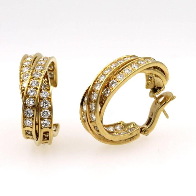 These timeless diamond in/out hoop earrings by Cartier are circa 1990's. The earrings feature 82 round brilliant cut diamonds that equal approximately 5.0 CTTW graded E/F color and VVS clarity.    Cartier's high quality and craftsmanship sets them