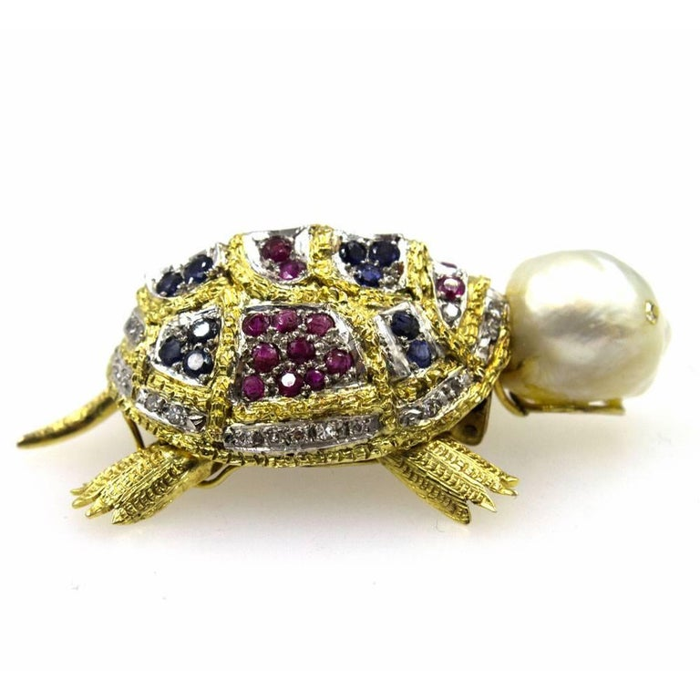 Absolutely adorable,  this vintage turtle brooch is hand crafted using diamonds, gemstones, and a pearl head. The pin is fashioned in 14 karat yellow gold and features mobile legs. There are 34 diamonds that equal approximately .36 carat total