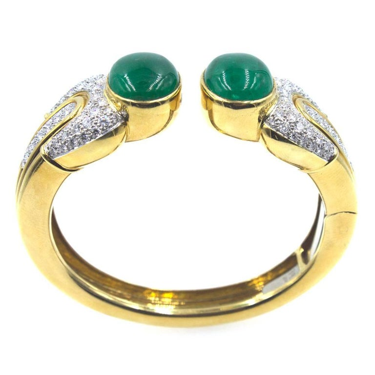 This fabulous 1970's cuff features two large cabochon emerald end caps. The emeralds weigh approximately 25 carat total weight. The hinged cuff is also crafted with textured 18 karat yellow gold and 124 round brilliant cut diamonds. The diamonds