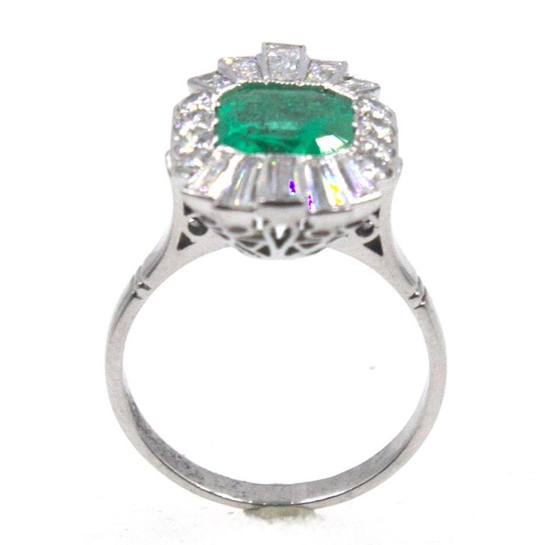 This fabulous emerald diamond cocktail ring is circa 1940's. The ring is crafted in platinum and features a 2.50 carat natural emerald surrounded by 1.35 carat total weight baguette cut diamonds. The top of the ring measures 15 x 20mm, and the ring