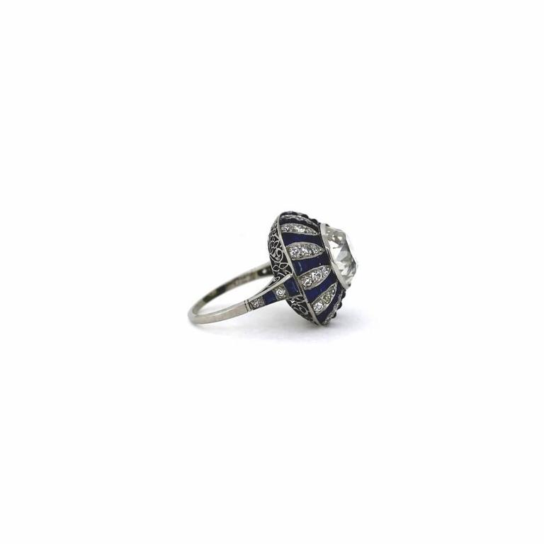 This is a Magnificent Art Deco Style Diamond and Sapphire Platinum Ring.  It features a center stone of a beautiful 5.70ct old european cut diamond GIA certified H color and VS2 clarity.  It is surrounded by small sapphires and diamonds weighing