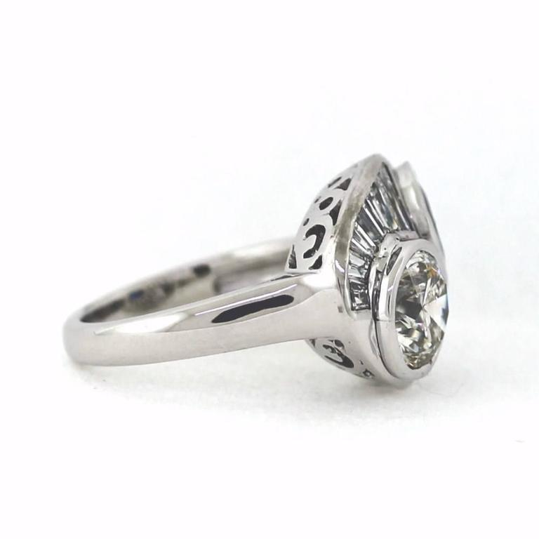 Top Notch 18K White gold construction with 2 main stones flanked by smaller diamonds. It contains 1 Round transitional Brilliant diamond = 2.19ct and 1 Round Sapphire = 2.50ct, with side diamonds broken down to 42 Round Brilliant = 1.26tcw & 14
