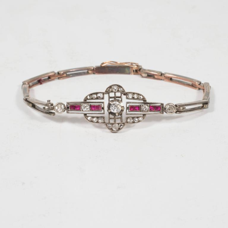 This stunning Victorian/Edwardian era gold bracelet handmade circa 1880 and purchased from the legendary 5th Avenue antique jewelry atelier James Robinson. The central pendant features five mine cut and eighteen rose cut white diamonds (weighing a