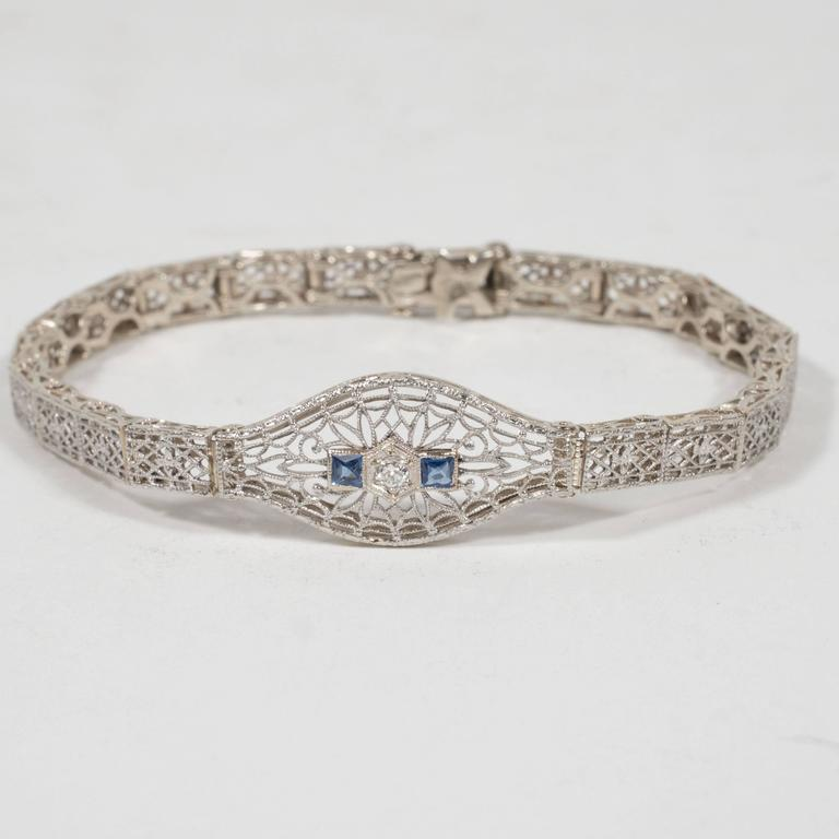 This gorgeous Art Deco bracelet features a central three point old mine cut diamond placed in a hexagonal shaped setting which is flanked by two square cut synthetic sapphires on either side. The central link offers a wealth of baroque patterns,
