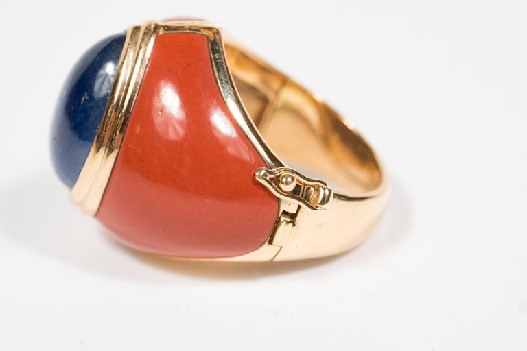 Hand crafted in France circa 1968, this sophisticated ring features a fine pear-shaped cabochon sapphire weighing approximately 12 carats, surrounded by 2 carved jasper plaques, all set in 18kt yellow gold.  The ring is hinged with a clasp to open