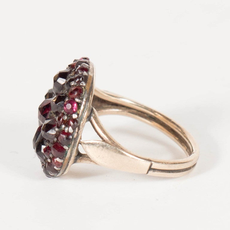 This elegant ring features a starburst design of garnets set in what is called a garnet gold setting which is sterling silver washed in 14k yellow gold.The ring is currently a size 6 but the buyer could easily have it sized by a local jeweler.