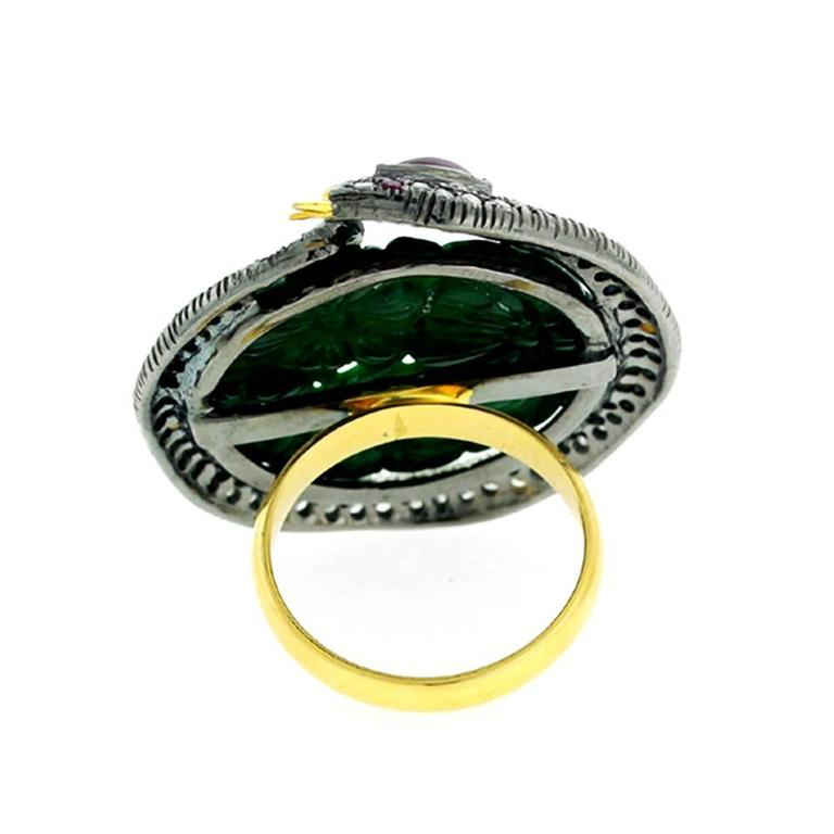 Very attractive and unique Jade and pave diamond on the snake motif wrapped around. Jade is carved with a bunch of flowers and is deep green color.  Ring Size; 7 can be sized  18k:2.8gms  Diamond: 1.1cts  Ruby:0.35cts Jade-13.60cts