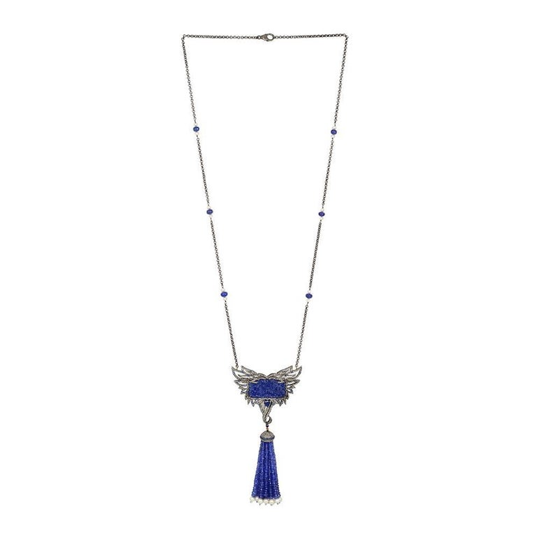 Luxurious looking this long necklace is elegant and a beauty, with carved Tanzanite with feather pattern set with Diamonds with a perfect tassel hanging down with Tanzanite and pearls strand.    Necklace Closure: Lobster Clasp  18Kt: 0.68g Diamond: