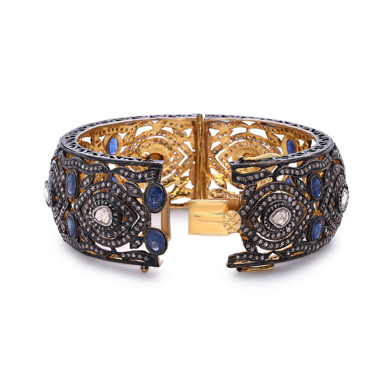Beautiful hand carved filigree work bangle set in Gold & Silver with Diamonds, Blue Sapphire & Rose cut Diamonds. It is an openable bangle with 2 safety clasps. 