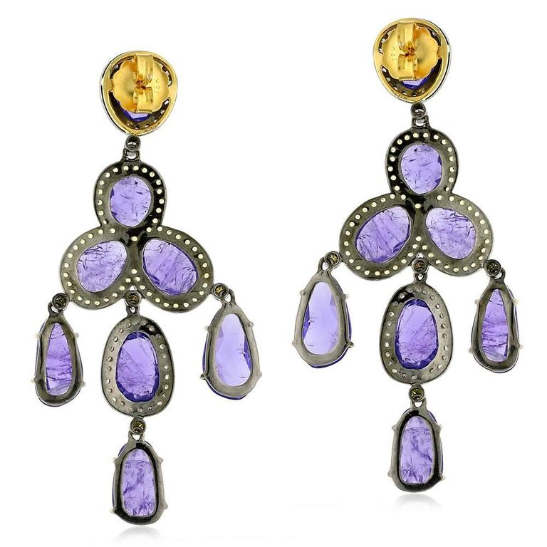 Simple and sleek Oval Tanzanite Chandelier earring with pave diamonds and yellow sapphire around.  Closure: Push Post  18kt:5.09gms Diamond: 1.38cts Silver: 8.08gms Yellow Sapphire:1.63ct Tanzanite:43.60ct