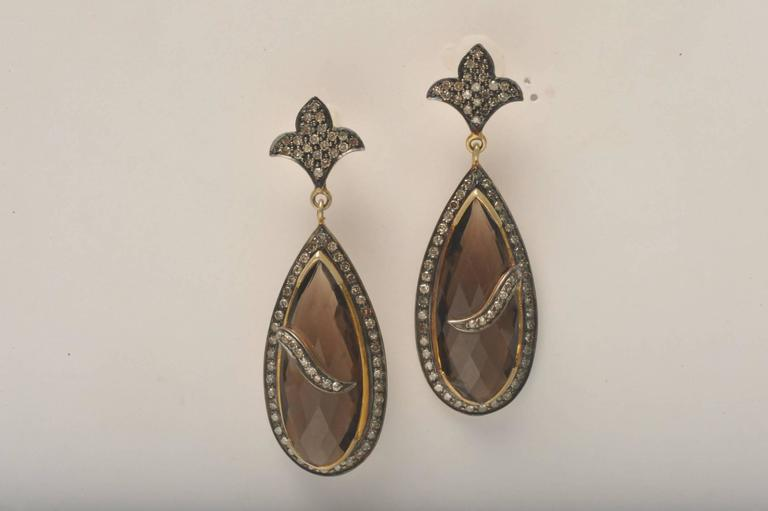 Pair of unusual faceted smokey topaz pear-shaped earrings with pave`-set diamonds set in 18K gold and sterling silver.
