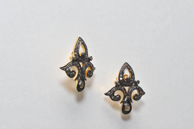 Diamonds set in oxidized sterling in a classic fleur de lis design with 18K gold post for pierced ears.  Carat weight is .87.