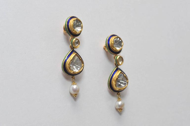 Beautifully crafted pair of rosecut diamonds set in 22K gold with kundan enamel work along the edges and along the backside with a drop pearl.  Indian made, late 1900's.  2.4 carats of diamonds.    Rare and unusual pieces of fine Indian jewelry.