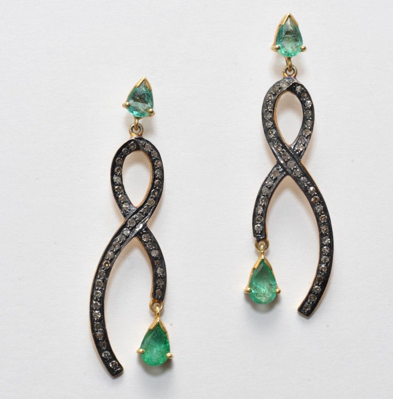 Pair of earrings with pear-shaped faceted emeralds set in 18K gold on the post and dangle.  The body of the earrings are pave`set diamonds in oxidized sterling.