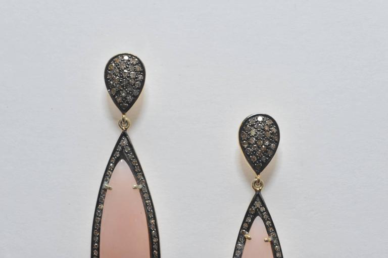 Pair of oval shaped pink opal drop earrings bordered with pave`set diamonds and diamonds on the post.  Set in oxidized sterling with 18K gold post for pierced ears.