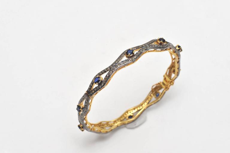 Faceted sapphires with pave`set diamonds set in oxidized sterling and 18K gold.  Hinged with push clasp and two safeties.  Carat weight of sapphires is 4.20; diamonds are 4.50 carats.  Inside circumference is 7 inches.  This was originally a pair,