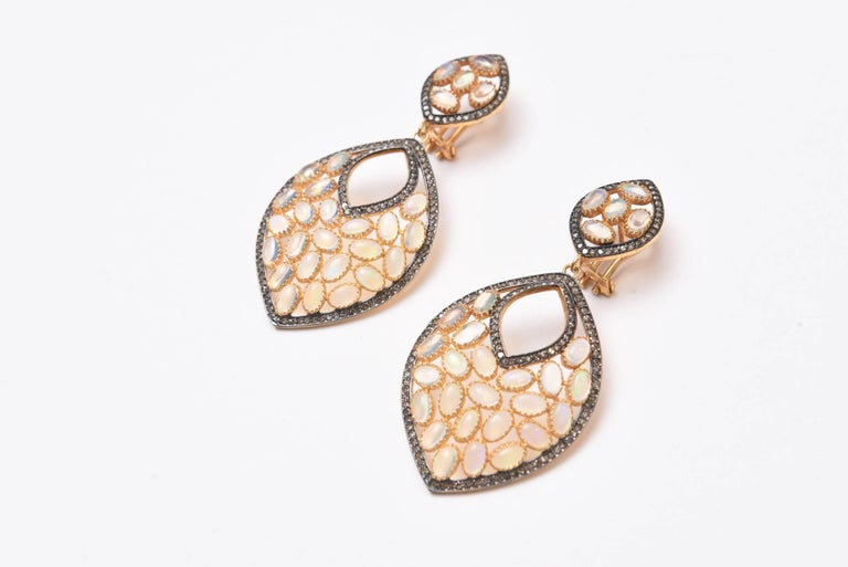 Pair of fabulous opal earrings with nice fire in the stones in a bezel setting and bordered with pave`set diamonds.  18K gold post with omega back for pierced ears, Oxidized sterling and vermeil.  Carat weight of opals is 8.08; diamonds are 1.56