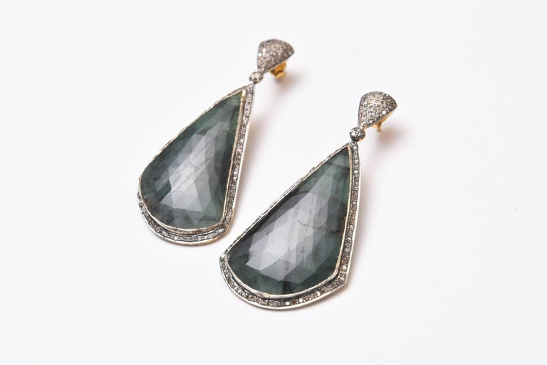 Extraordinary size of rose cut emeralds in their natural state bordered in pave`set diamonds in sterling silver.  Diamonds on the post as well with 18K gold earring posts for pierced ears.  Emeralds are 50.75 carats and diamonds are 1.90 carats.