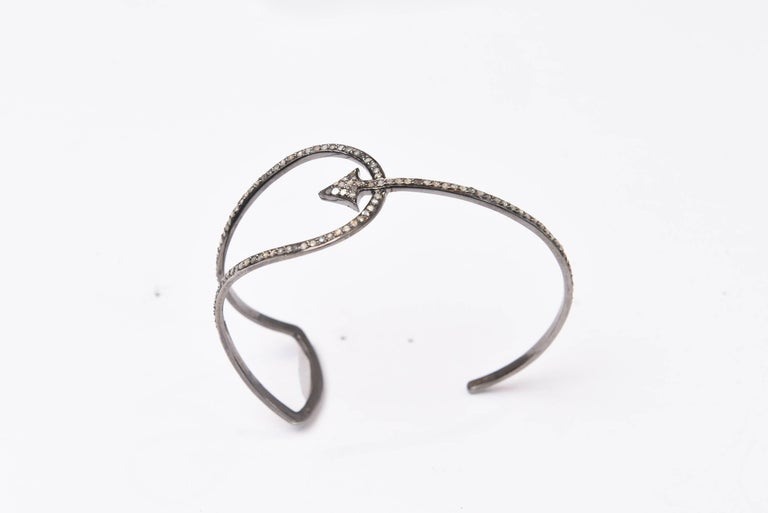 This is a very cool cuff bracelet.  Pave`-set diamonds 3/4 of the way around set in an oxidized sterling silver featuring a pierced arrow motif.  Carat weight of diamonds is .78.  Inside circumference is 6.50 inches with a degree of flexibility as